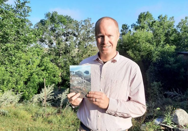 """FRANK JOHNSON, formerly of Hallock, shows his newly published book, """"Rocks and Roots:Reflections on the Superior Hiking Trail."""" (Submitted photo)"""