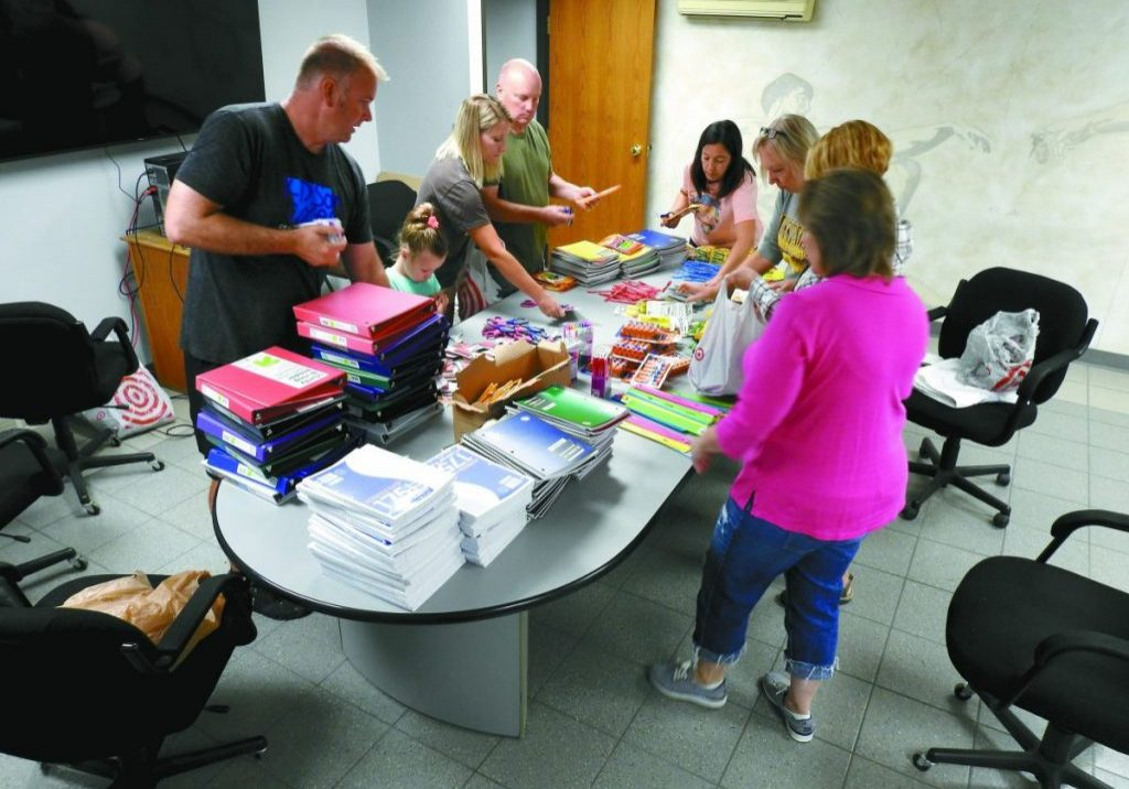 VOLUNTEERS HELPED PACK SUPPLIES into backpacks to give to students around Kittson County last week. These bags are provided by KIDSon Cares. Clockwise from left: Jacob Hook, Ceres Grant, Leanna Lindegard,David Lindegard, Cheri Bakken, Diane Younggren, Julie Lindegard and Jillayne Kraska. (Enterprise photo by Anna Jauhola)