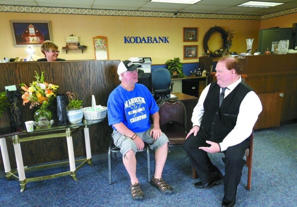 TOM SILEWSKI, right, visits with Cecil 'Butch' Fossell during an open house honoring Silewski for his 40 years as a banker in Kennedy. Fossell trained in Silewski as a banker when he started withFarmers State Bank in 1981. In the background is Tracy Larson, also a KodaBank employee. (Enterprise photo by Anna Jauhola)
