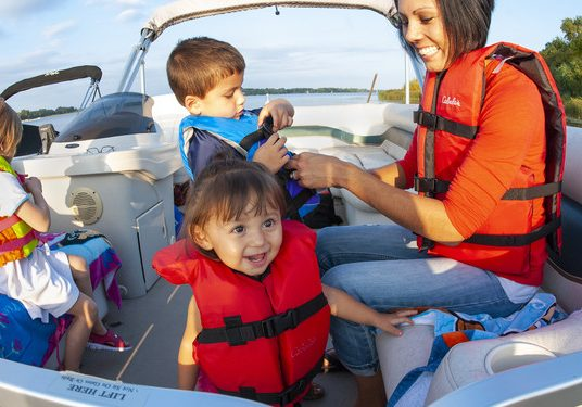 Mom helping her kids put their life jackets on, pontoon boat